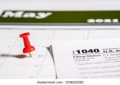 Calendar with pushpin inserted in the date for May 17 to illustrate the new tax return filing date of f17th May 2021.
