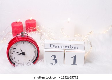 Calendar and red clock - symbol of  New Year, fairy lights  and birning candles  on white fur background. Winter holidays concept. Time concept.