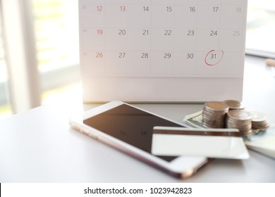 calendar with red mark on date 31 to remind of payment time and smart phone, credit card and money on table