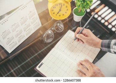 Calendar reminder event concept.Woman hand planner or organizer writing on diary book and 2019 Calendar page.Student planning appointment,noted and count Down schedule day on Calender.