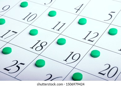 calendar sheet at an angle on which the tablets are on each date. pills green to take daily contraception