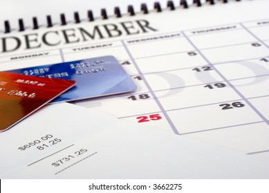Calendar showing Christmas holidays, a bill for several hundred dollars, and a couple of credit cards.