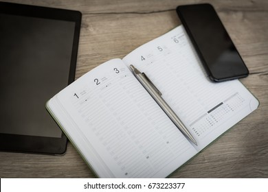 Calendar table photo with metal pen. Wooden office background banner with smartphone, tablet and calendar. New year 2017 2018. Business background.