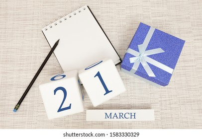 Calendar with trendy blue text and numbers for March 21 and a gift in a box.