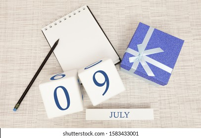 Calendar with trendy blue text and numbers for July 9 and a gift in a box.