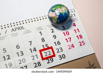 calender on pink background, earth day holiday. Marked date April 22. top view