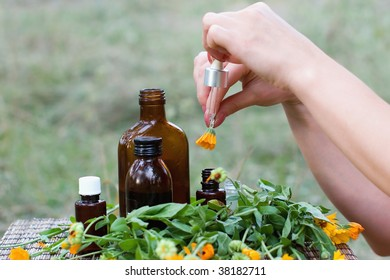 Calendula flowers and aromatherapy essential oil and tincture in glass bottles.