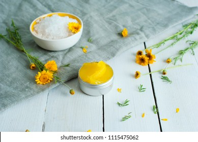 calendula medical cream and bath salt, flowers on gray canvas, white wood background