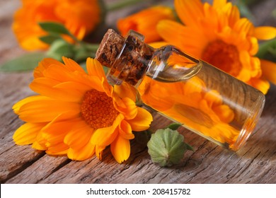 Calendula oil in a glass bottle on an old table closeup horizontal