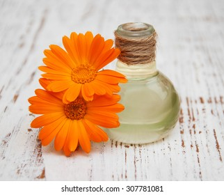 calendula oil in a glass bottle on a old wooden background