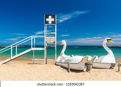 Caleta de Fuste, Fuertaventura, Canary Islands - September 9 2018: Baywatch tower and fun boats at Caleta de Fuste Beach