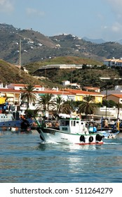 CALETA DE VELEZ, SPAIN - OCTOBER 27, 2008 - Traditional fishing boats in the harbour with town buildings to the rear, Caleta de Velez, Malaga Province, Andalusia, Spain, Europe, October 27, 2008.
