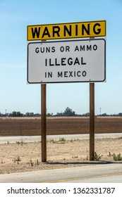 CALEXICO, CA - APRIL 6, 2019: A warning sign at the US Mexico border stating Guns or Ammo illegal in Mexico.