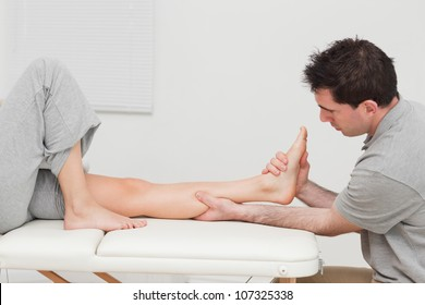 Calf of a patient being massaged by a physiotherapist in a room