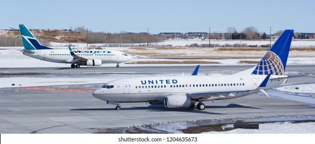 CALGARY, AB - March 23, 2018 A WestJet Boeing 737 and a United Airlines Boeing 737 taxi at Calgary International Airport