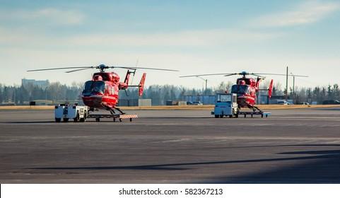 CALGARY, AB - NOV 27, 2016. Two STARS Air Ambulance BK-117 helicopters standby at Calgary International Airport
