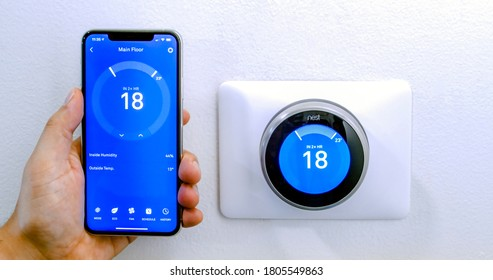 Calgary, Alberta, Canada. Aug. 29, 2020. A person cooling down with air conditioner with a iPhone 11 Pro Max using the nest app on celsius metrics using a wireless Nest Learning Thermostat.