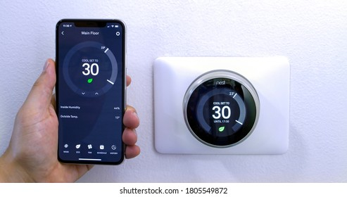 Calgary, Alberta, Canada. Aug. 29, 2020. A person saving energy with a iPhone 11 Pro Max using the nest app on celsius metrics using a wireless Nest Learning Thermostat on a white wall.