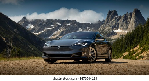 Calgary, Alberta / Canada August 14th 2019 : Photograph of a Tesla model 3 in front of a mountain in the wilderness of Canada.