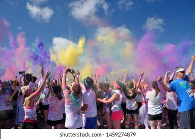 Calgary, Alberta, Canada August 3, 2013: People covered in colorful powder as the run, large number of people raising their hands up in excitement as clouds of colorful dusts exploded in the air.