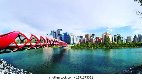 Calgary, Alberta, Canada - July 19, 2018: Panoramic view of red colour Calgary Peace Bridge with tall skyline in the background