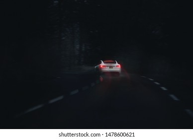 Calgary, Alberta / Canada July 8th 2019 : Photograph of a Tesla model 3 driving in the dark with light trails.
