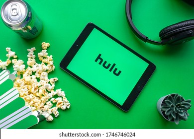 Calgary, Alberta. Canada. June 1 2020. An iPad with the Hulu logo on the screen on a green background with popcorn and headphones