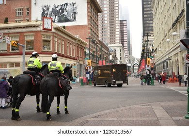Calgary, Alberta / Canada - November 2nd 2018: A pair of policemen on horse back riding down Stephen Avenue and 1st Street in downtown Calgary.