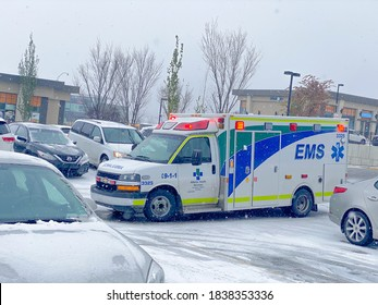 Calgary, Alberta, Canada. Oct 20, 2020. An Emergency Medical Services Ambulance 9-1-1, Alberta Health Services waiting for a patient during snow fall during the winter.