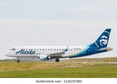 CALGARY, ALBERTA - JUNE 28, 2018: Alaska Airlines, operated by Horizon Air, N628QX Embraer E75L preparing to depart Calgary International Airport