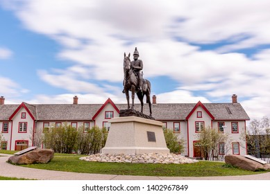 Calgary, Alberta - May 8, 2019: Statue of Colonel James Macleod in front of Fort Calgary. The red and white building is in the background. Day time longe exposure.