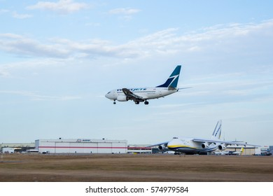 Calgary, Alberta - November 9, 2016. An Antonov AN-124 aircraft holds short of the runway at Calgary International Airport shortly before departure as a WestJet 737 lands