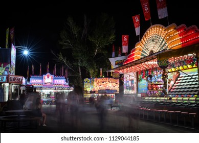 Calgary, Alberta/Canada - July 7, 2017: People stand, sit or walk around the Calgary Stampede Midway grounds in the concession and games areas. People that are moving are only showing up as ghosts.