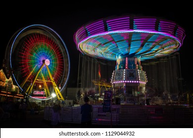 Calgary, Alberta/Canada - July 7, 2017: People stand around or enjoy midway rides at the Calgary Stampede midway grounds.