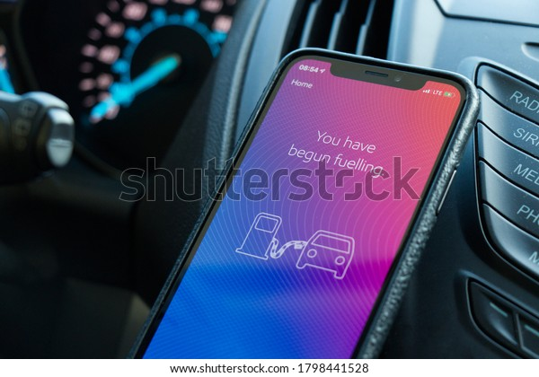 """Calgary, Canada - April 19,2020: A view of  phone inside the car with Esso&Mobil Speedpass+ App which says """"You have begun fuelling"""". Pay for fuel using your smartphone."""