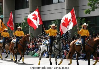 CALGARY,  CANADA - JUL 9, 2004  - Yellow women riders with Canadian flags on horseback,Calgary Stampede Parade,  Alberta, Canada