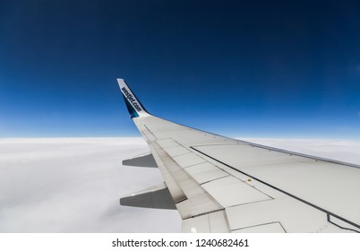CALGARY, CANADA - July 7, 2018 : Wing of WestJet Airlines flying above the clouds. people looks at the sky from the window of the plane, using airtransport to travel.