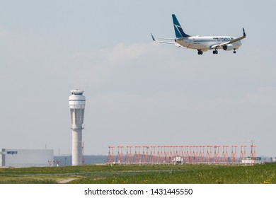 CALGARY, CANADA - JUNE 3, 2019: WestJet Airlines C-GOCD Boeing 737-800 coming into land at Calgary International Airport with the ATC tower in background.