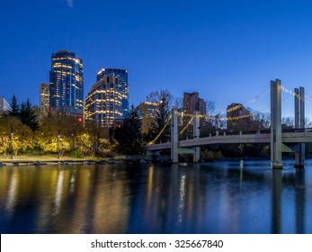 CALGARY, CANADA - SEPT 26: Skyscrapers tower over urban park space along the Bow River in the city of Calgary on September 26, 2015. The park is in the Eau Claire district of Calgary's urban centre.