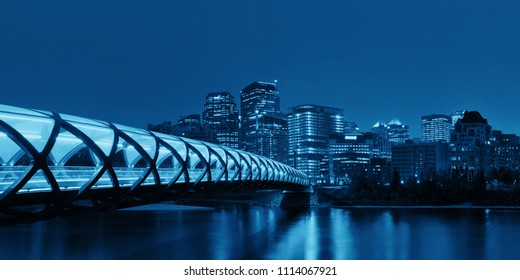 Calgary cityscape with Peace Bridge and downtown skyscrapers in Alberta at night, Canada.