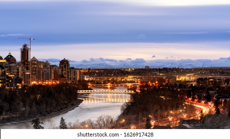 Calgary at night, Alberta, Canada. Peace Bridge over Bow River at night, Calgary downtown at night autumn with river in foreground and mountains in background