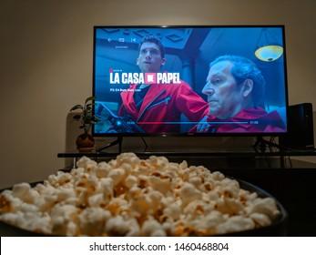 "Cali, Colombia - July 22, 2019: Netflix app on tv screen playing ""La Casa de Papel"" (Paper House) behind a bowl of popcorns."