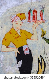 CALI, COLOMBIA, MARCH 4: Graffiti art and street murals of retro portrait of a beautiful pin-up woman serving up soda drinks painted by unknown artist on vintage wall. Colombia 2015