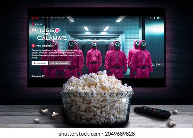"""Cali, Colombia - September 28, 2021: Netflix app on tv screen playing """"El Juego del calamar"""" (Squid Game) behind a bowl of popcorn and a remote control."""