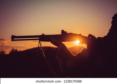 Calibers of hunting rifles. Rifle Hunter Silhouetted in Beautiful Sunset. Silhouette of the hunter. Pulled the trigger of the shotgun. Barrel of a gun