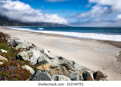 California beach. Miles of white sand. Boulders in the foreground with colorful ice plant. Location: Stinson Beach, north of San Francisco.