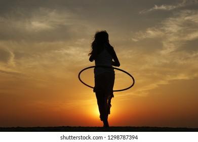 California beach sunset. hula hoop dance on California beach. beautiful girl dancing on a sandy beach. California beach girl