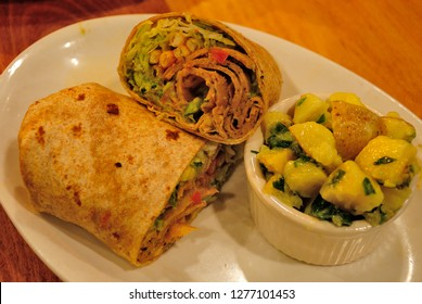 California Burrito made with seitan,  shredded romaine lettuce, melted American cheese, salsa, guacamole, and  sour cream and wrapped in a whole wheat tortilla, served with young potato salad