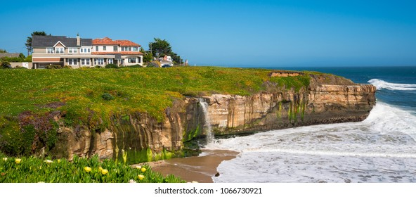 California coastline with a waterfall in spring with blue sky