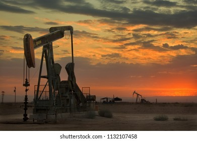 California crude oil wells, energy, and fossil fuel industry, with background of setting sun.